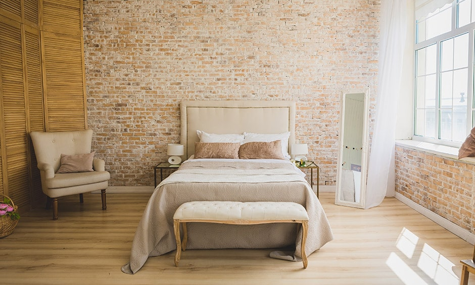 Rustic style minimalistic bedroom design with a queen-sized wooden bed and an exposed brick wall