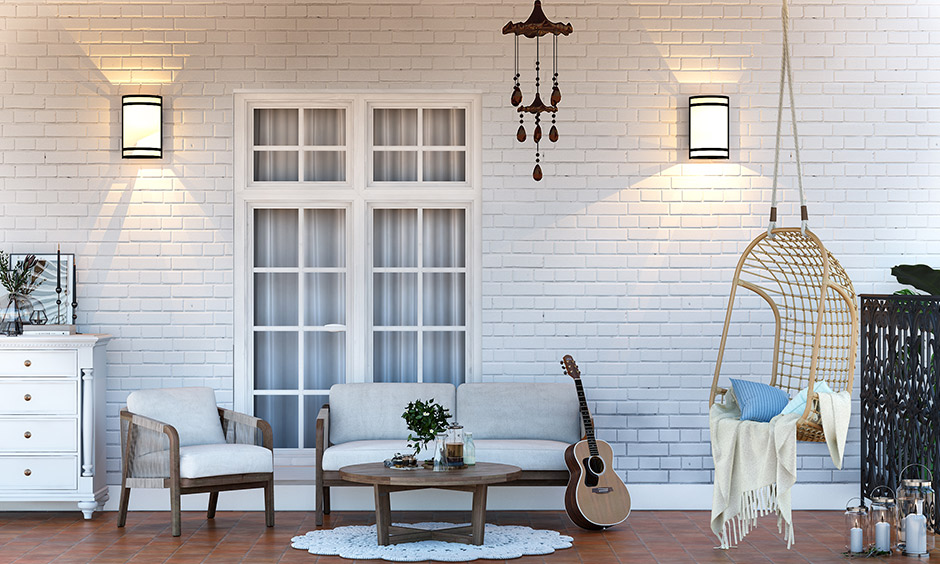 Snow-white wall, sofa, wooden swing and an antique-looking wind chime makes a perfect classic home porch design.