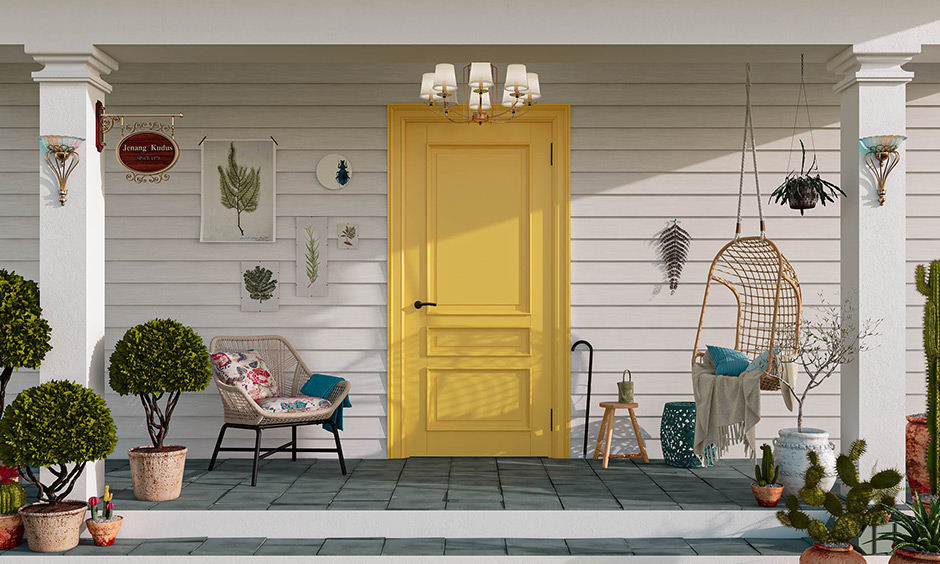 Yellow-painted front door, chandelier and wall-mounted lamps add a warm and inviting feel to this house front porch design.