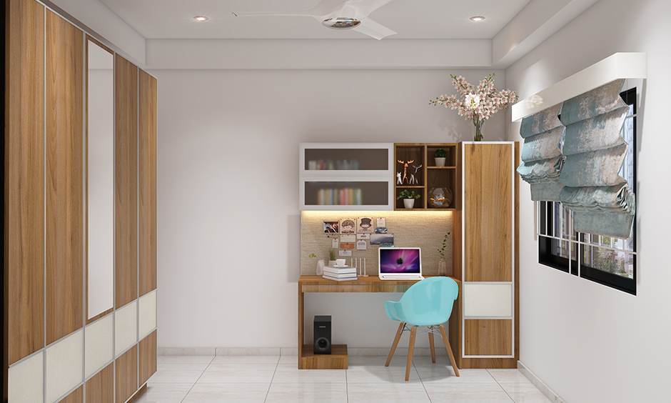 Teenage bedroom interior design in Bangalore with a backlit study unit and popping blue armchair looks gorgeous