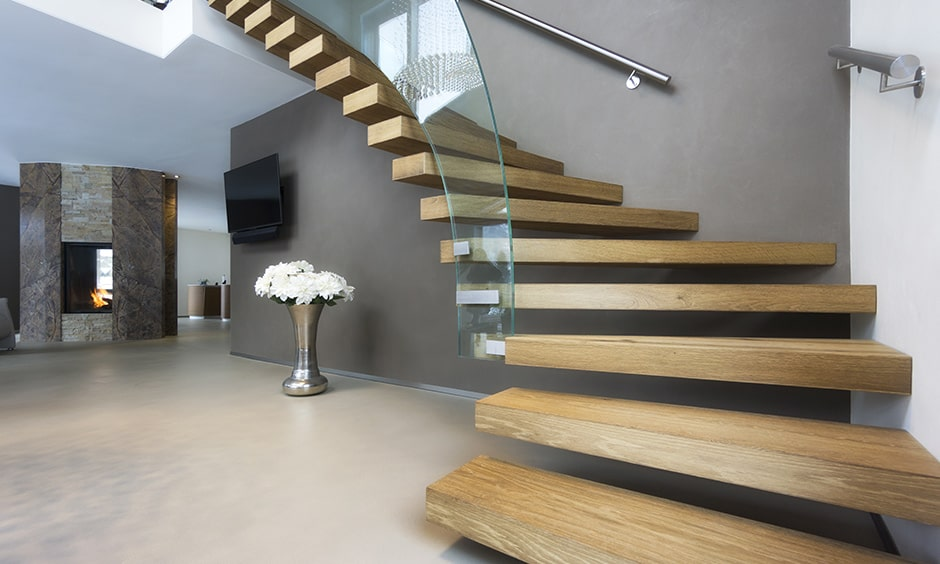 Twisted wooden staircase with floating steps and a glass railing brings a modern wooden staircase design
