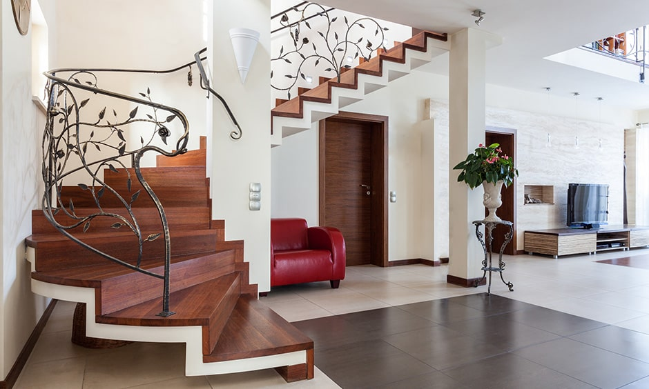 Wooden staircase with an elegant railing adds to the luxury look for indian homes