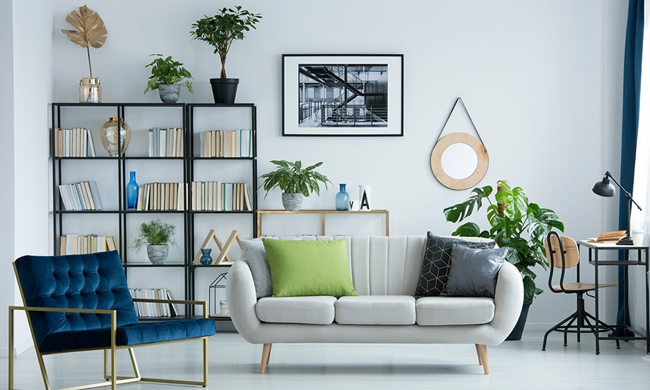 Home library idea in a white living room with corner library and a rich blue armchair