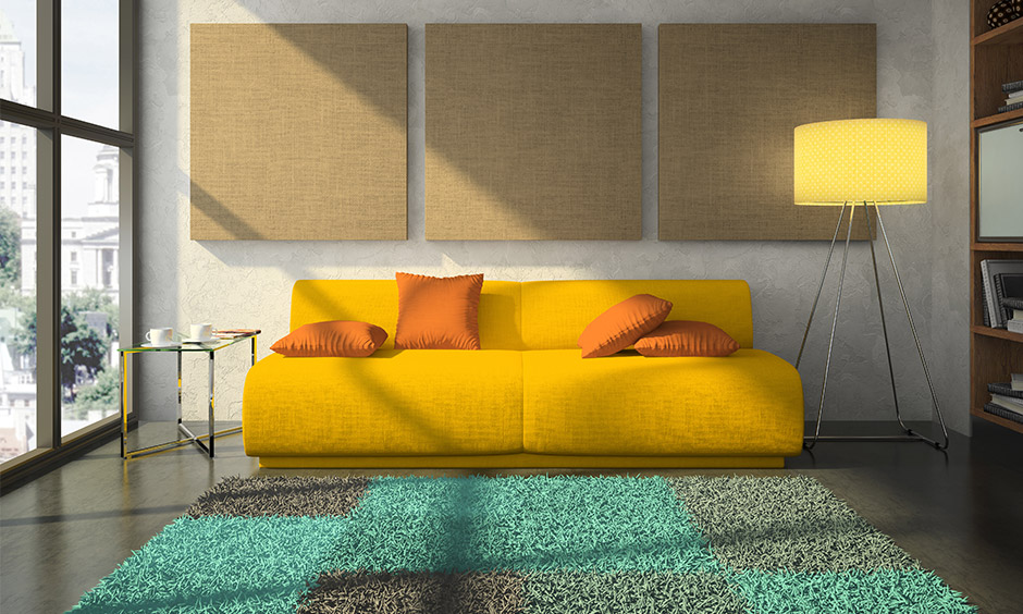 Beige wall and splashes of yellow such as a sofa with orange cushions feel summery & bright in beige and yellow living room