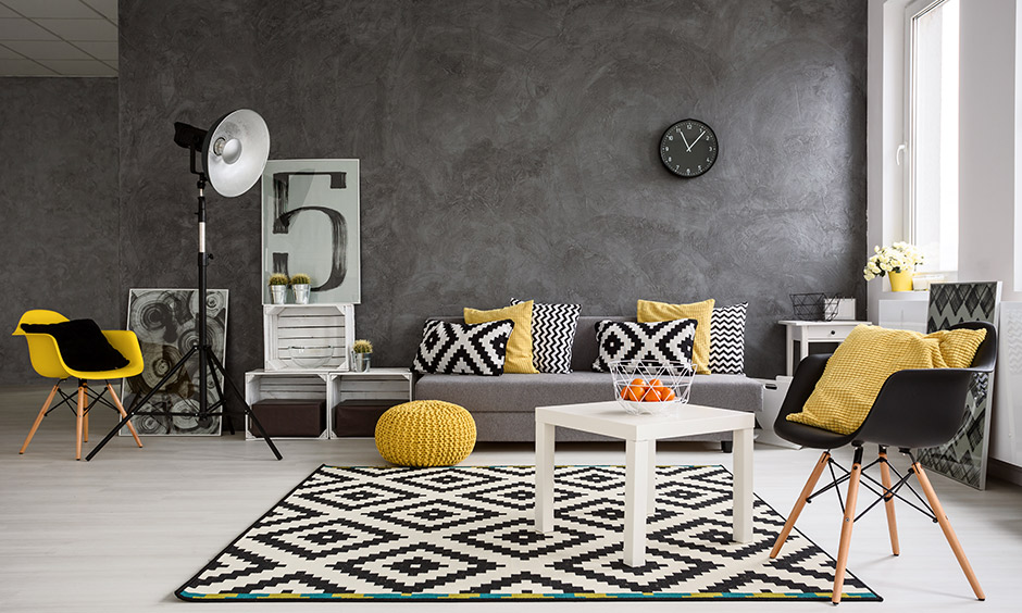 Black and yellow living room ideas, black wall and pops of a yellow pillow & chair bring out something different and unique