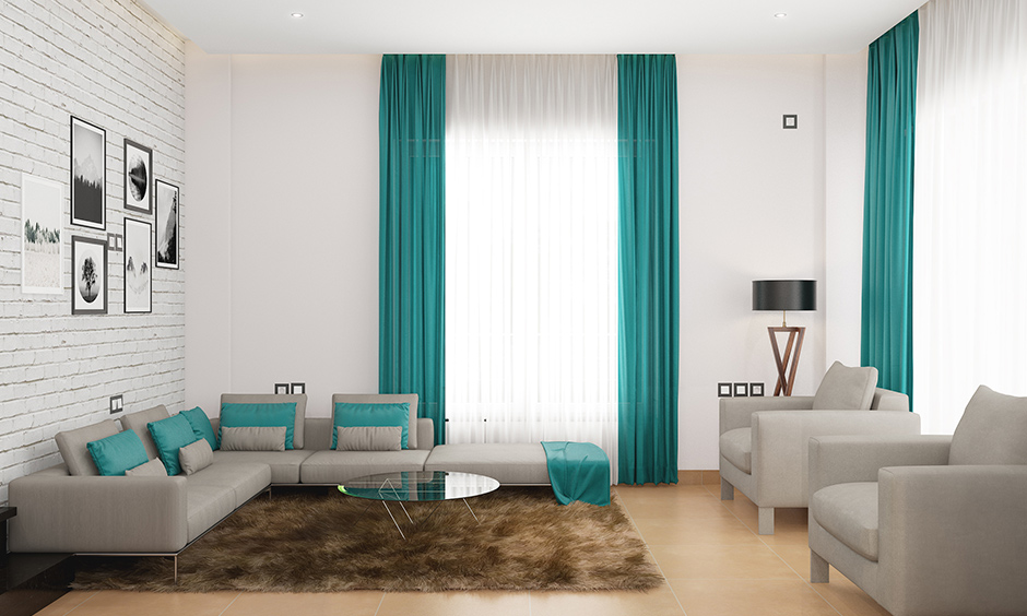 A breezy beachy white sofa living room with blue curtains, plush pillows and wooden flooring