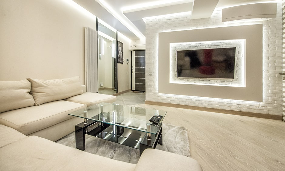 Contemporary living room with metallic accent wall and statement lighting