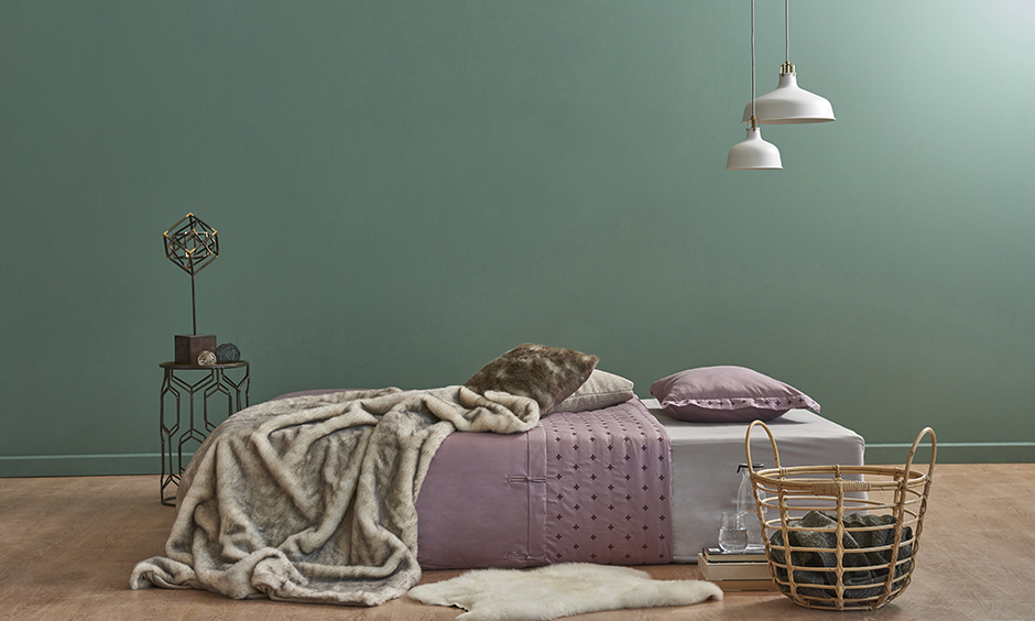 Green and lavender bedroom with unique light fixtures and a furry rug