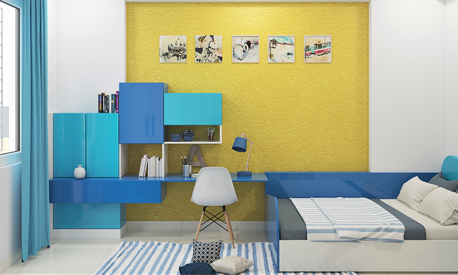 Blue and yellow themed room with a small bed for sleeping as well as seating and abstract wall art are dorm room ideas.