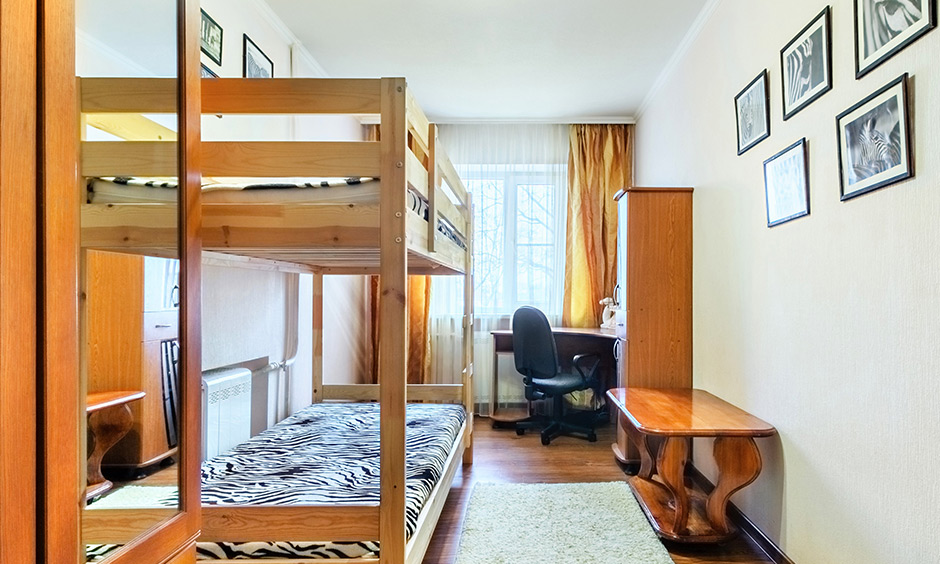Wooden bunk bed, side table, almirah, desk and a soft, fluffy floor rug are simple dorm room ideas.