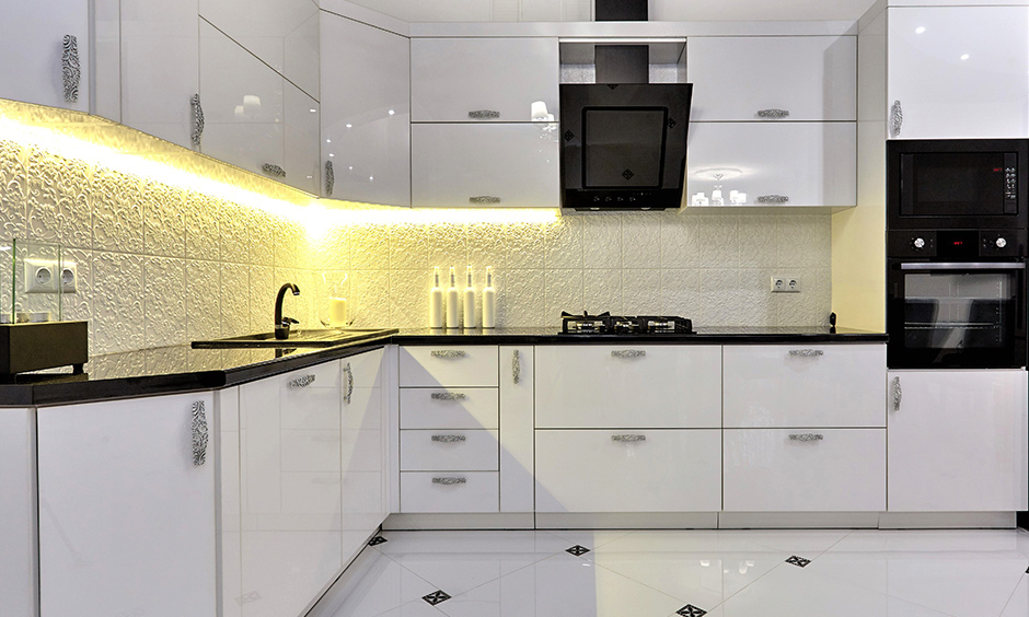 White-themed, lacquered corner unit kitchen cabinet with LED lighting under cabinet exudes freshness and brightness.