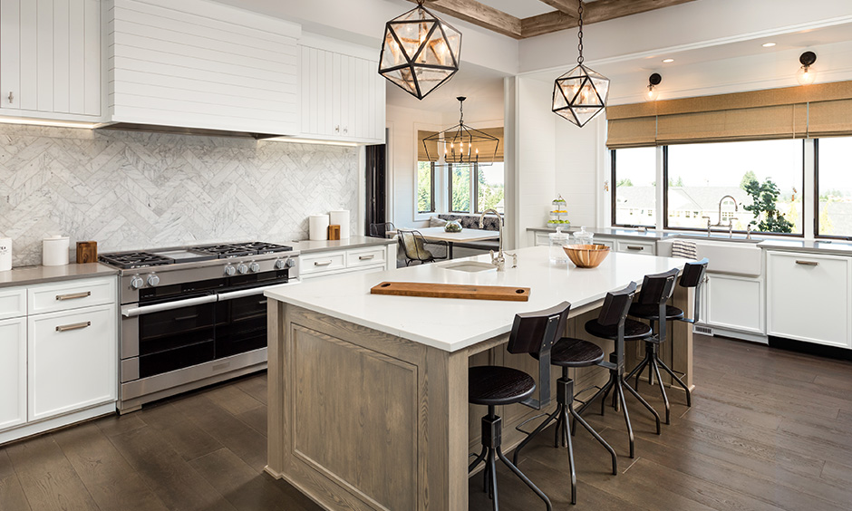 This kitchen island lighting has drop-down light above a countertop & antique candle styled light above a dining table.