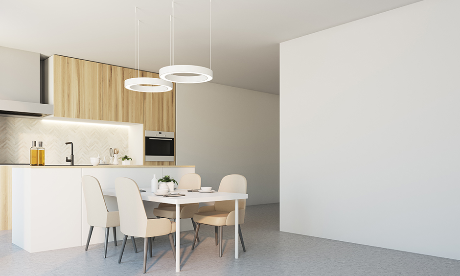 Modern minimalistic led kitchen lighting with dining table above it drop-down ring-shaped light add to the aesthetic