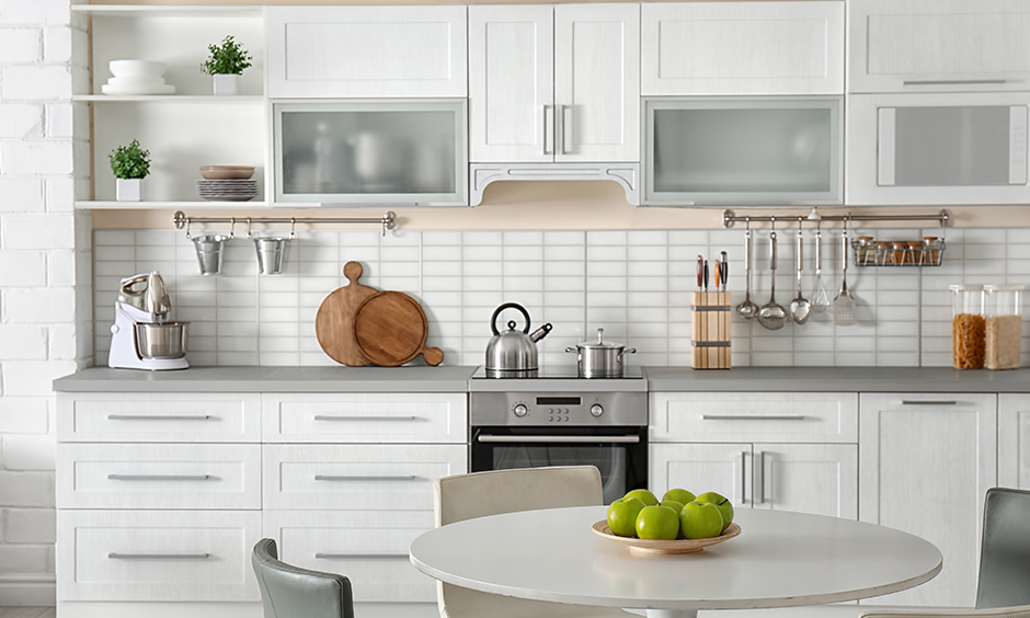 One wall kitchen ideas with a dining table, sleek grey countertop and a white tiled backsplash look elegant.