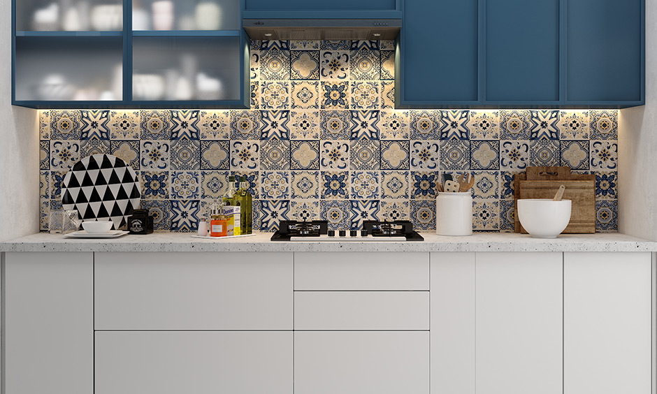 Single wall kitchen in bold blue and white with a pretty floral tiled backsplash and cabinets look gorgeous.