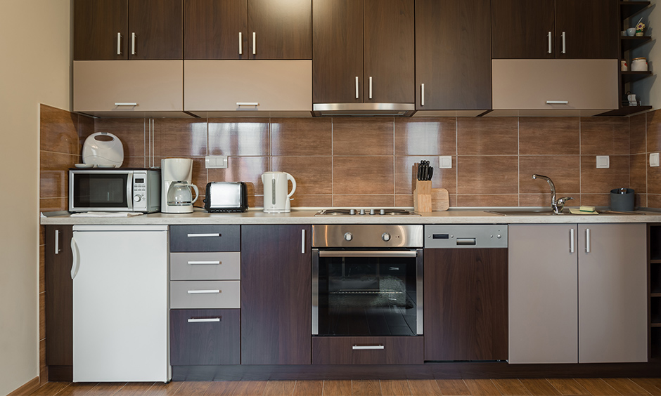 Shades of brilliant brown tiny one wall kitchen have space for a mini-fridge and cabinets to store crockery.