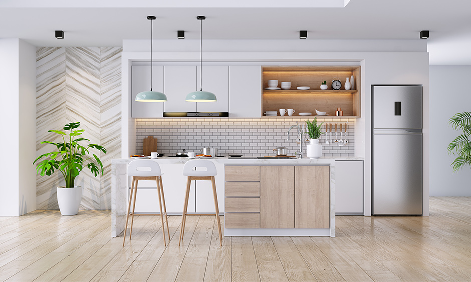 White & woody one wall kitchen with island, brick backsplash, cabinets & pair of pendant light looks elegant.