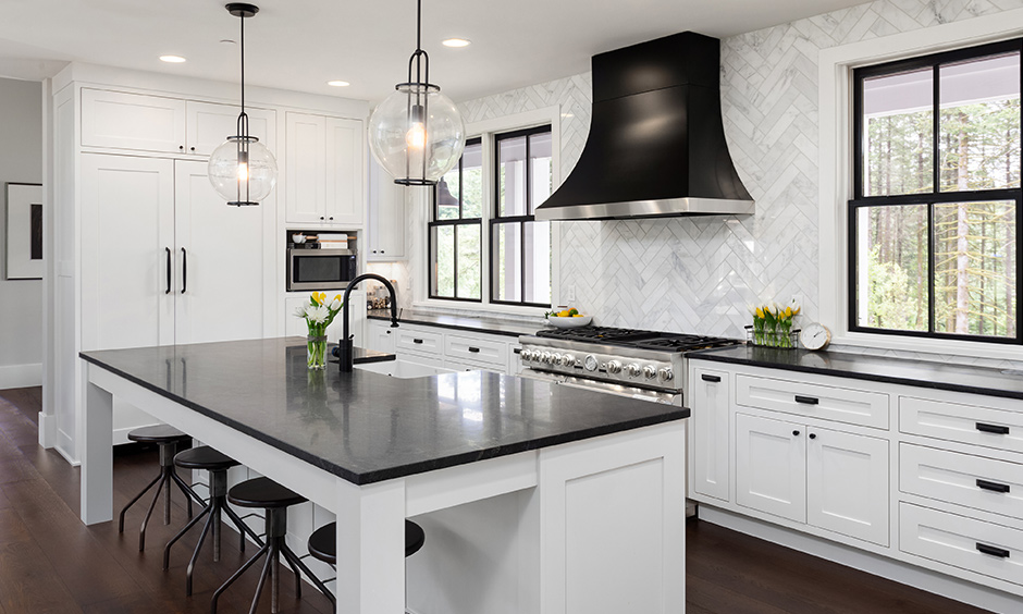 Black marble countertops with with white cabinets and and bar stools around the kitchen islands
