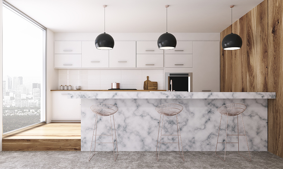 Neutral coloured marble countertop cost with black pendant lights and water resistant with smooth surface in kitchen