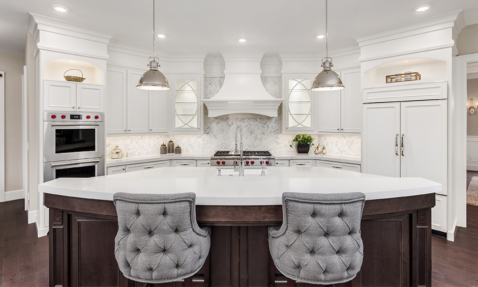 White luxury marble kitchen with a bar counter in an arch shape & domed shaped pendant lights looks elegant.