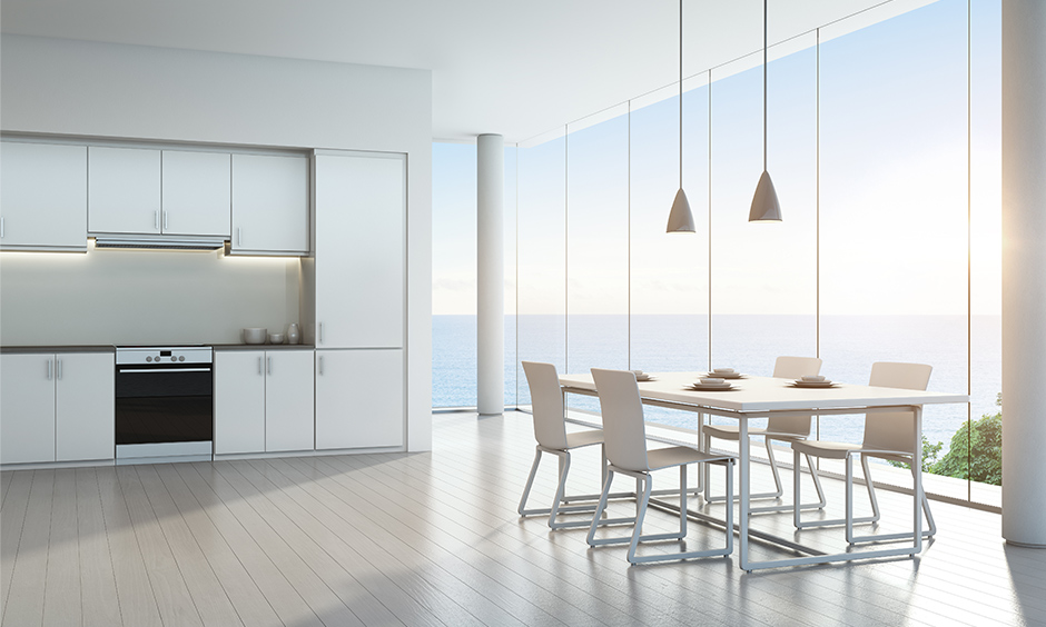 White luxury modern kitchen designs with large bay windows will leave you with a beautiful sea view & blue sky.