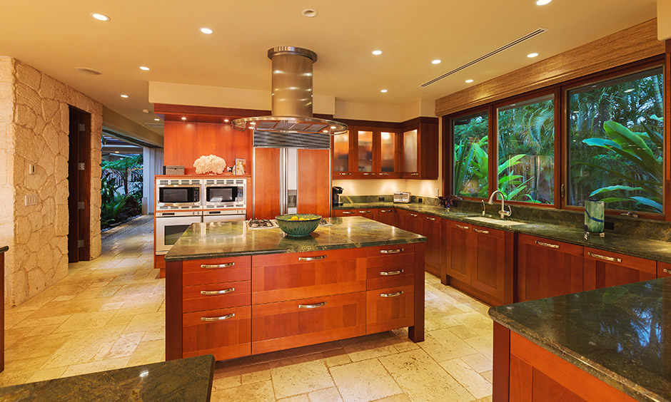 Luxury designer kitchens with wooden island & large windows with a view of trees outside give rustic rainfall feel.