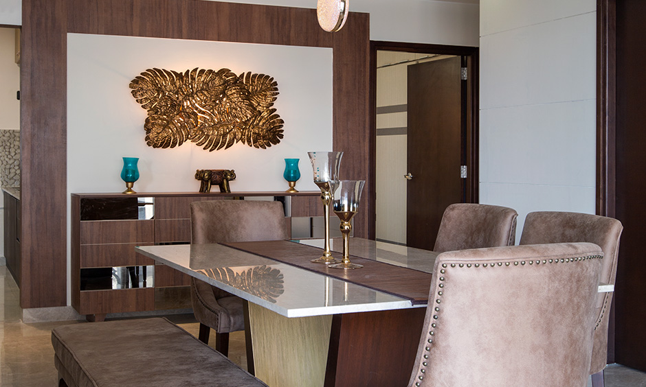 4bhk dining room designed with frosty white countertop and dark wood at the bottom is famous interior designers in Bangalore
