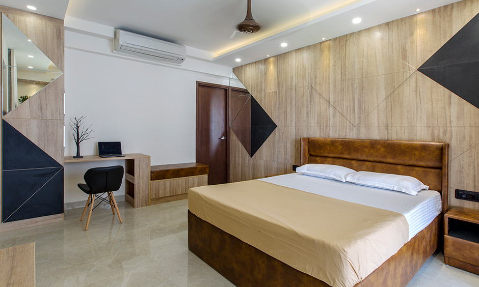 Design cafe's interior design studios in Bangalore designed this 4bhk flat bedroom with a study table with a rustic finish.