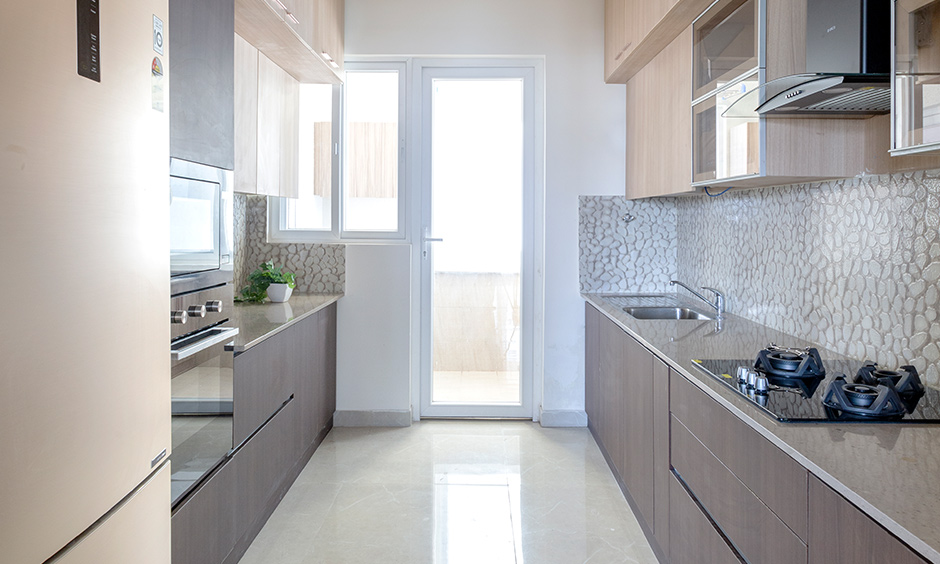 4bhk flat interiors with a parallel shaped kitchen consists of two countertops facing each other are the best interiors in Bangalore.