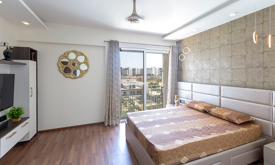 This Guest room has wooden flooring, wall mirror & rustic square wallpaper are the best interiors in Bangalore.
