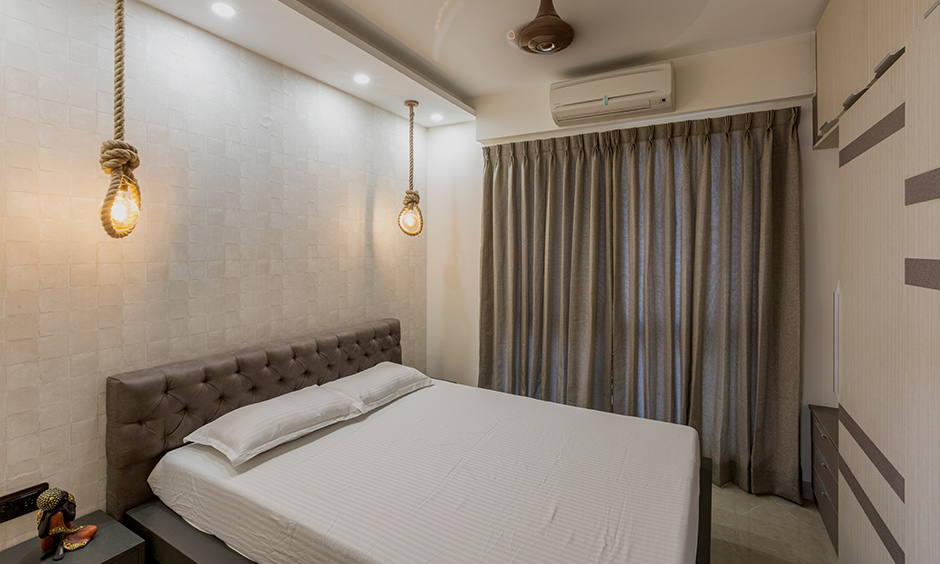 This 4bhk flat bedroom has a stone textured wallpaper & rope knot pendant lights are interior designs for Divyasree 77 place.
