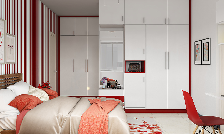 Frosty white framed in red kids wardrobe designs with plenty of space for storage & dressing mirror is perfect.