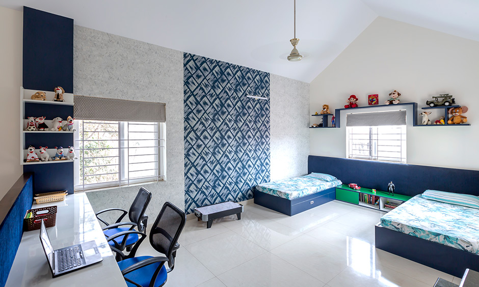 DC best interior designers in sarjapur road designed this kids room with study table, blue pattern wallpaper & blue beds.
