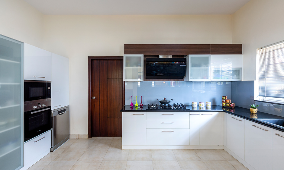 White u-shaped kitchen designed by dc interior designers in sarjapur road with all the essential storage looks modern.