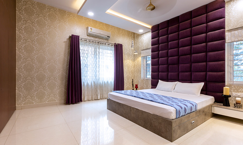 Master bedroom with purple upholstered headboard & gold wallpaper intricate Victorian pattern interior design Bangalore Sarjapur Road.