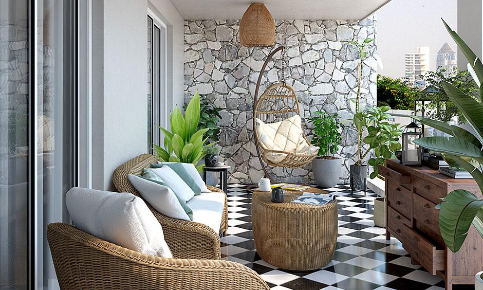 Küçük balkon mobilyası hasır kanepe, eski bir masa ile eşleştirilmiş bir masa ve bazı basit iç mekan bitkileri modern bir dokunuş katıyor.