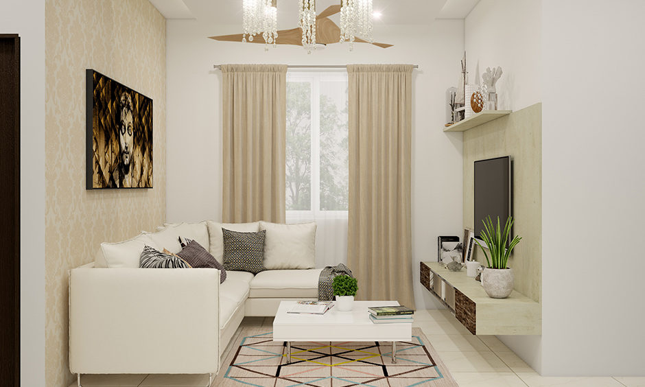 Light-hued living room decor with a long chandelier completes and looks modern.