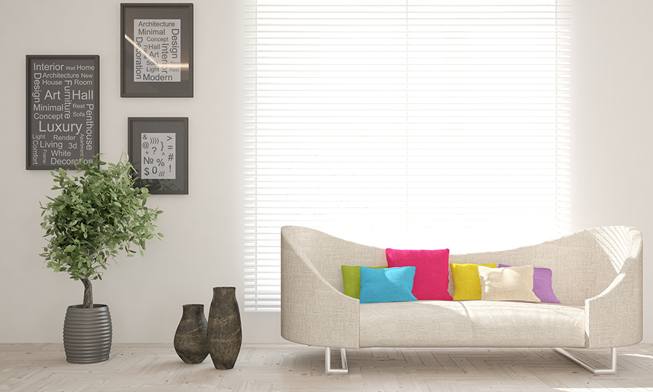 A frosty white sofa with pretty coloured plush pillows on furniture cleaning easy and quick.