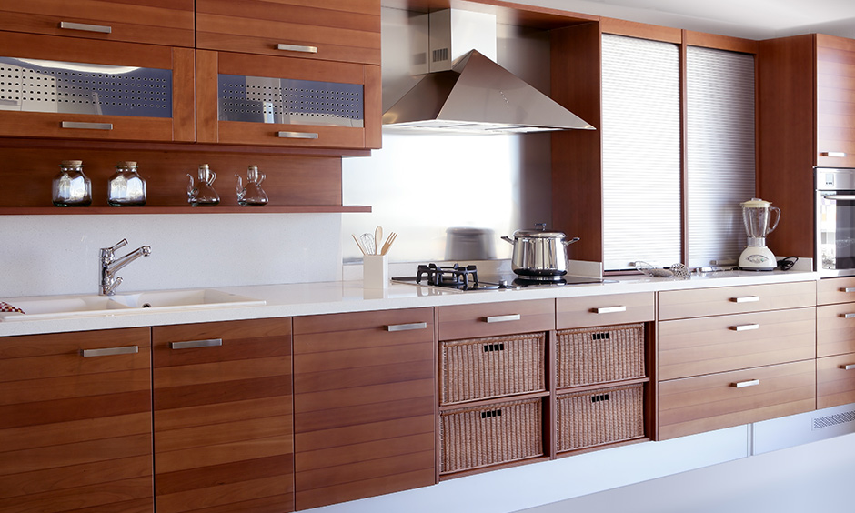 Blend of traditional & modern wood kitchen cabinets with lift-up cabinets, drawers, & wicker basket more storage options.
