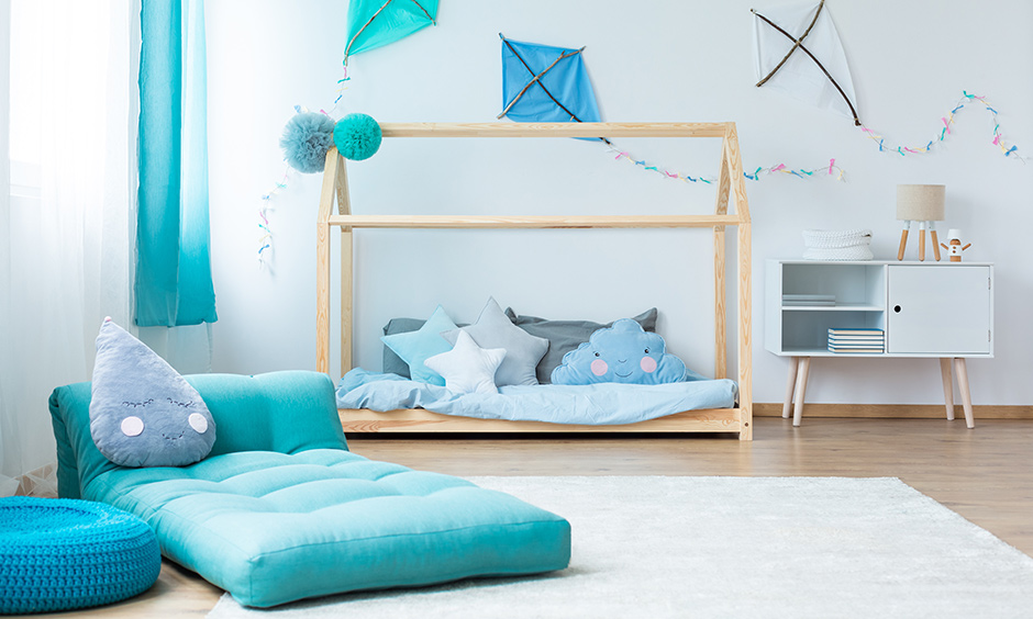 Beautiful room with daybed and bean bag in blue and a white wall decorated with DIY kites are DIY bedroom decor crafts.