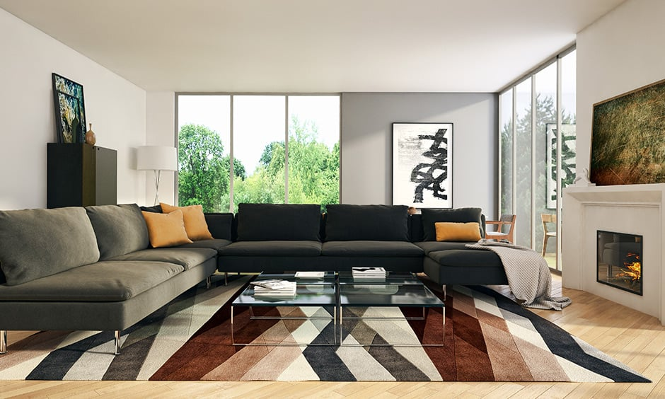 White walled living room with black & dark grey sofa set colour combination & yellow pillows brings in a fun twist.