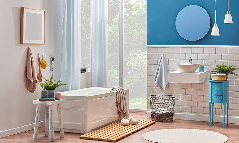 Plants around the bathtub in a white and blue stool with drawers are bathroom decor accessories that look gorgeous.
