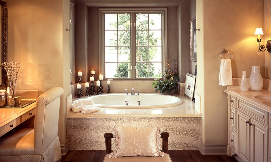 An elevated jacuzzi next to windowed bathroom decor with scented candles and ceramic pots looks classic.