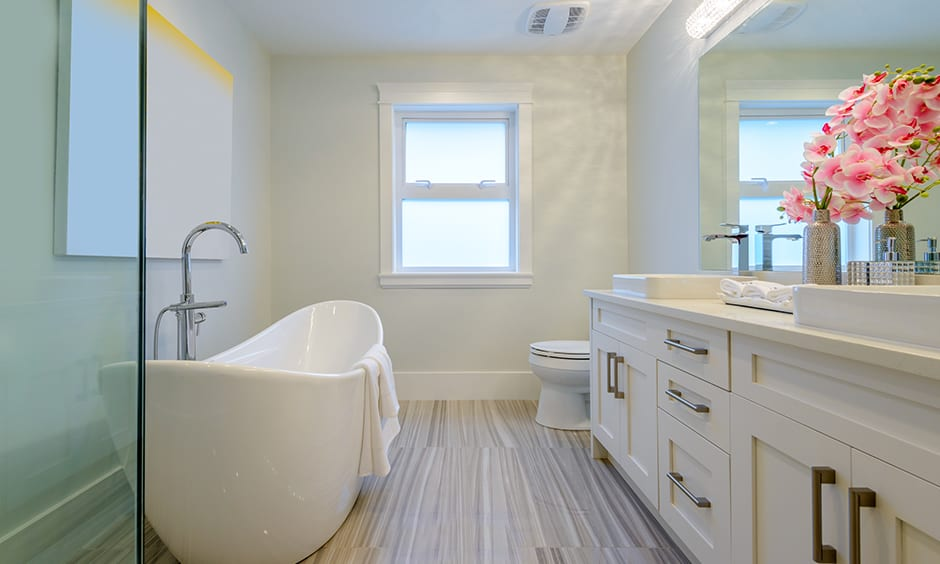 White bathroom with light wood flooring & a white ceramic tub is simple bathroom decor that looks elegant.