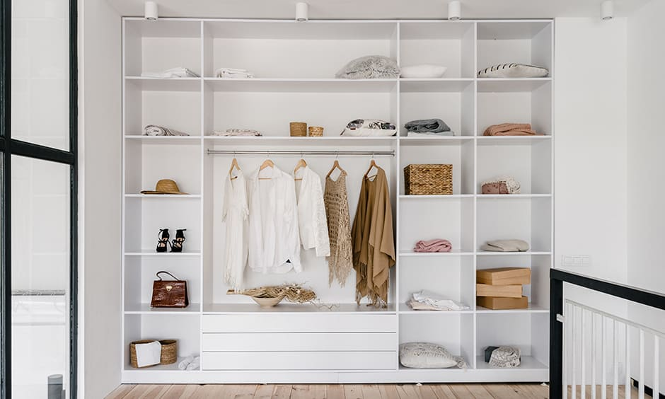 Minimalist women wardrobe designed in white colour with its finely divided storage option looks elegant.