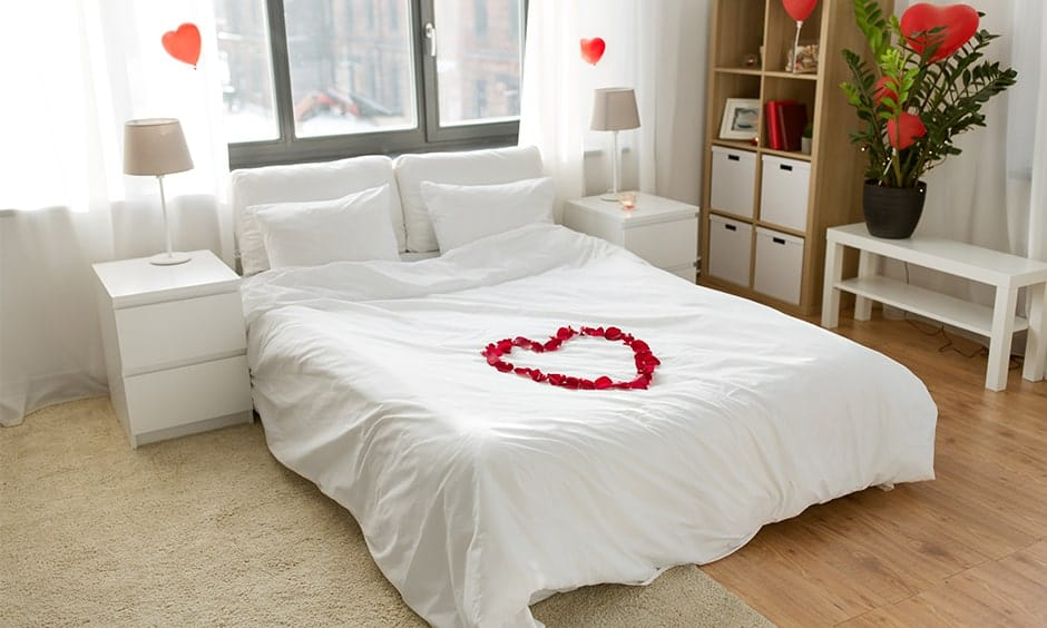Best romantic decor idea for your bedroom with white bedding and a heart-shaped balloons