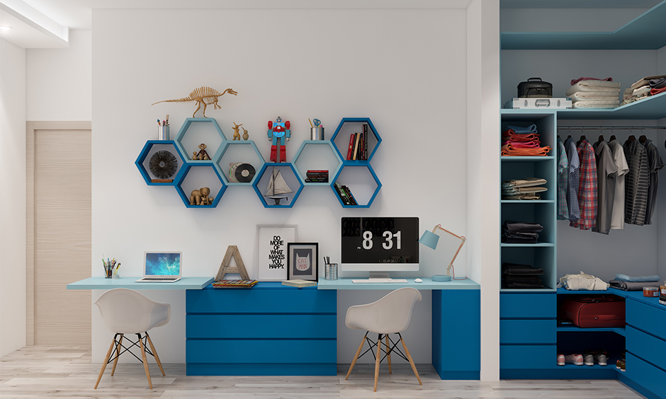Kids room study desk in blue colour designed for two kids with wall-mounted shelves looks chic.