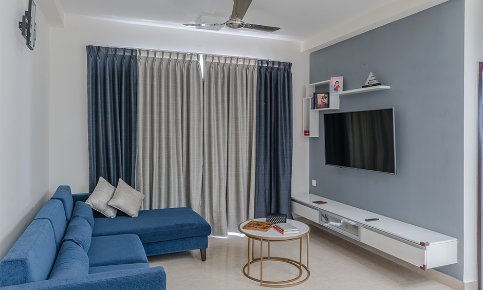 Design cafe interior designers in Kanakapura Bangalore designed this minimalistic living room with a wall-mounted floating TV unit.