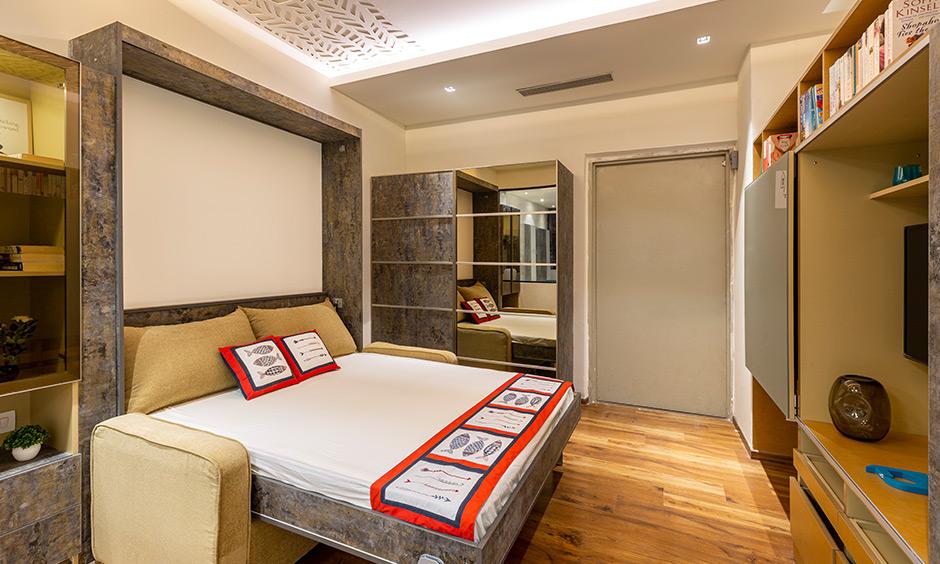 An eclectic theme guest bedroom with pull-down bed and hidden tv unit is interior design ideas in Hyderabad.