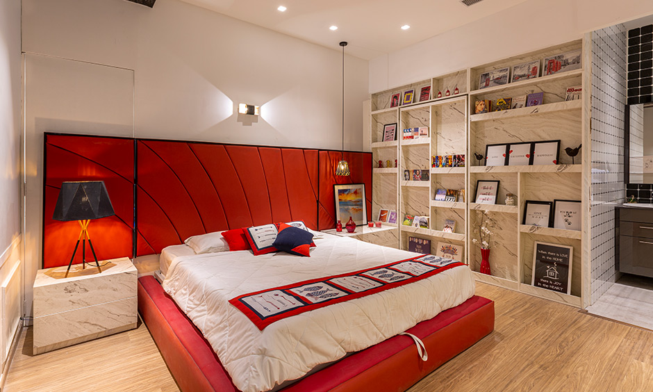 Large headboard master bedroom in a bold modern lux theme with books & photo storage is best home interiors in Hyderabad.